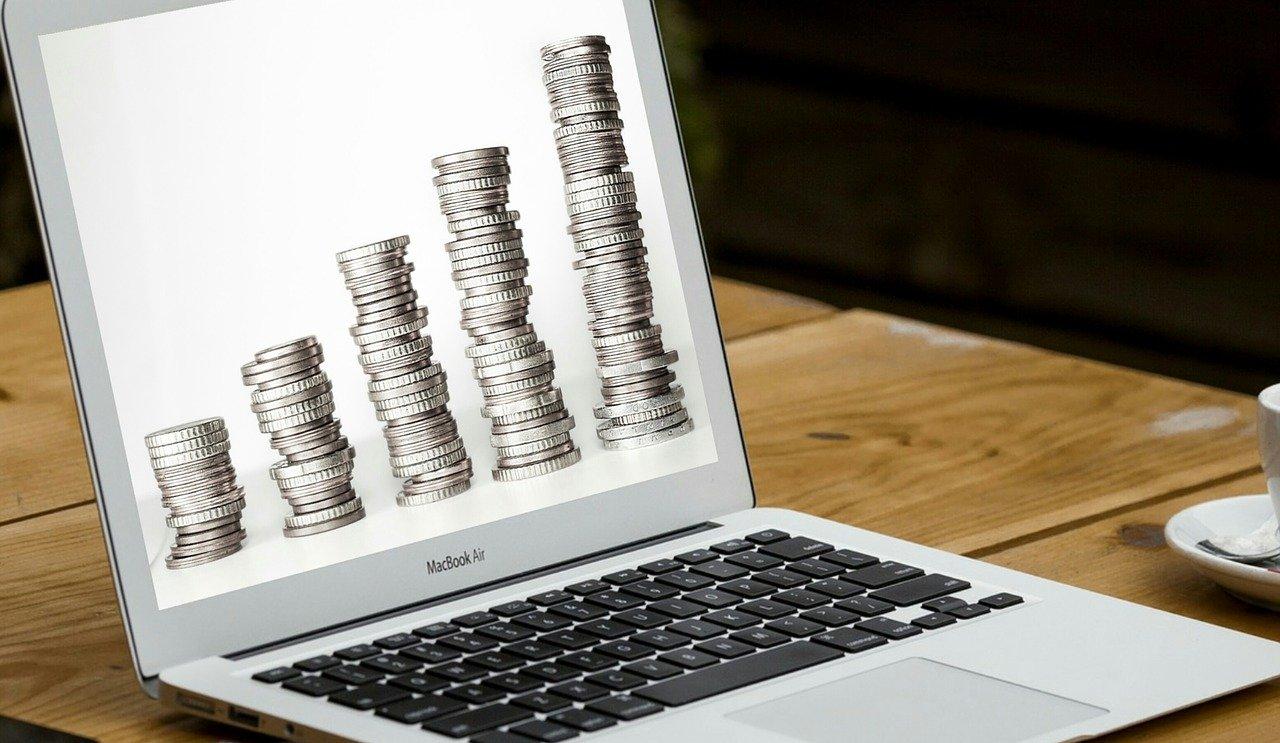 Un écran de pc portable avec des pièces de monnaie en fond d'écran